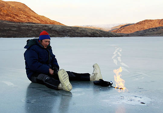 A researcher sits on the surface of an Arctic lake
